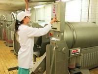 Технолог цеха по выработке копченостей устанавливает программу для массирования деликатесов на вакуумном массажере Meat Master